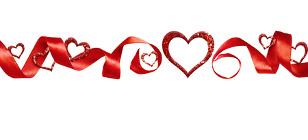 Red silk twisted ribbon and glitter hearts isolated on white background. Decoration for Valentine's Day. Stock Photo