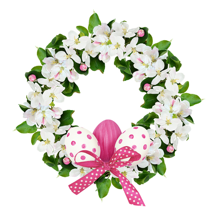 Round wreath with apple tree flowers and Easter eggs isolated on white background.