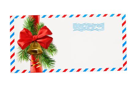 Leerer Umschlag mit roten und blauen Rändern und Briefmarke mit Schleife und Weihnachtsschmuck auf weißem Hintergrund gebunden. Ansicht von oben. Flach liegen.