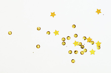 Golden seqines and stars scattered on white paper background 版權商用圖片
