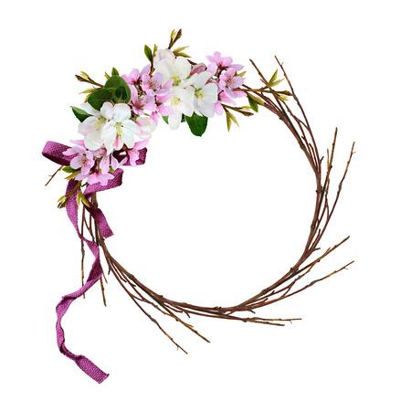 Corona redonda de ramitas secas con ramas de primavera de melocotón y flores de manzana lazo de cinta aislado sobre fondo blanco. Foto de archivo