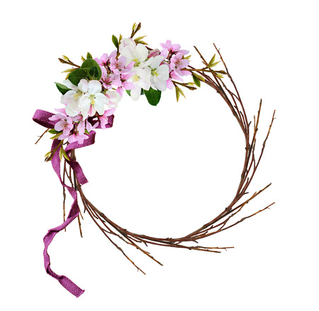 Round wreath from dry twigs with spring branches of peach and apple flowers ribbon bow isolated on white background Imagens