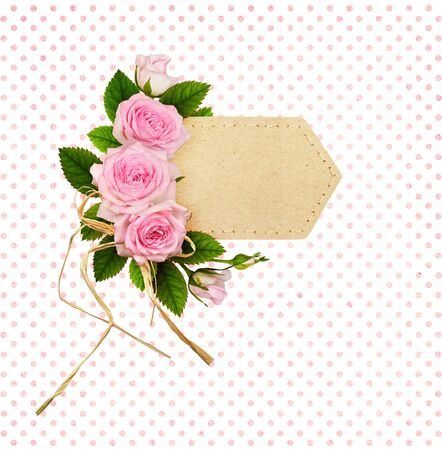 Pink rose flowers with raffia bow in a floral arrangement on craft paper label