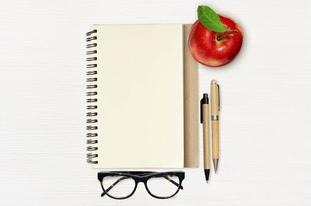 Empty notebook page, red apple, pens and glasses on white wooden background. Top view. Flat lay.