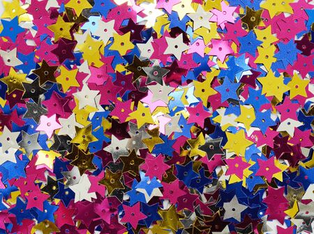 Scattered colorful star shape sequins for holiday background Фото со стока