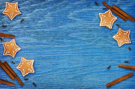 Ginger cookies and fragrant Christmas spices on blue wooden background. Top view. Flat lay.