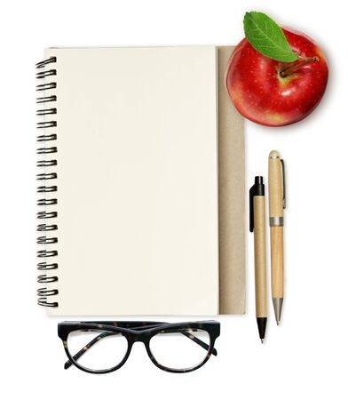 Empty notebook page, red apple, pens and glasses on white backgeound. Top view. Flat lay.