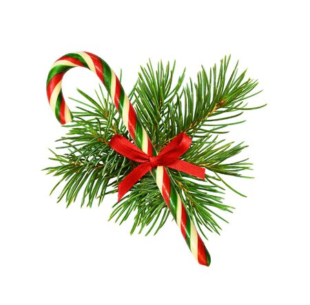Traditional Christmas cane with pine twigs and red silk ribbon bow isolated on white