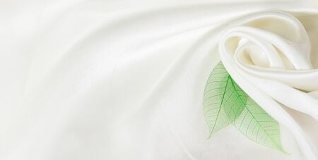 White silk background with drapery and green leaves