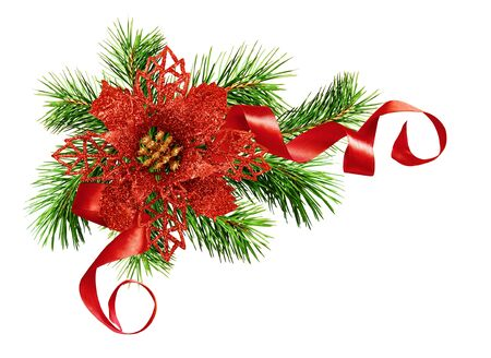 Artificial red glitter poinsettia flower, green pine twigs  and silk ribbon in Christmas corner arrangement isolated on white background