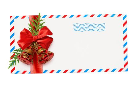Empty envelope with red and blue borders and stamp tied with ribbon bow and Christmas decorations isolated on white background. Top view. Flat lay.
