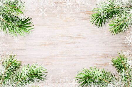 White painted wooden board with green pine twigs for holiday background