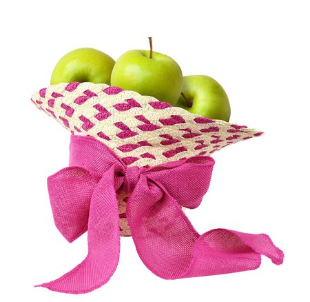 Inverted straw hat with pink canvas ribbon bow and green apples isolated on white background 版權商用圖片