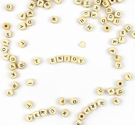 Lettering ENJOY with wooden beads on white background
