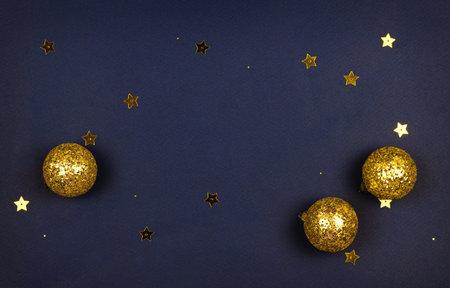 Golden Christmas decorations on dark blue paper background