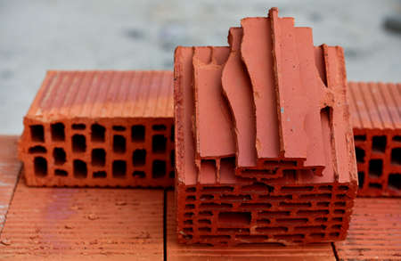 Red hollow wall brick in the context. The pile of red hollow bricks lit. Material for construction and repair, brick texture, preparation for the construction process