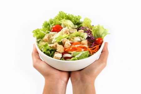 hand holding in a bowl of salad