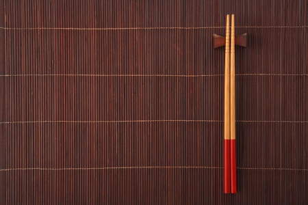 china cuisine: Two chopsticks on a bamboo mat