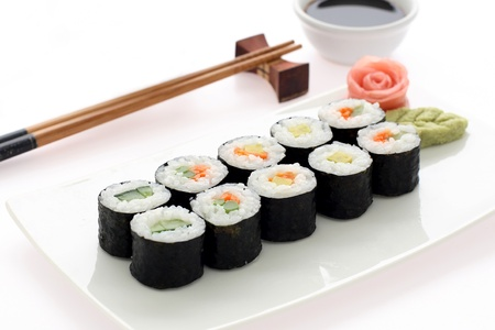sushi plate: Makizushi. Delicious sushi rolls on white plate with chopsticks and wasabi. Maki