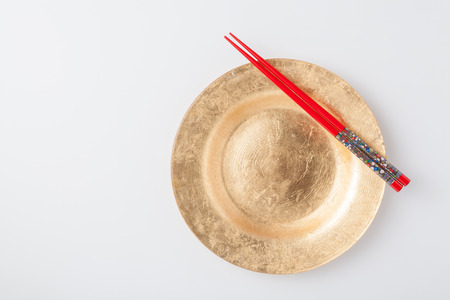 Empty plate and chopsticks. Isolated on white background