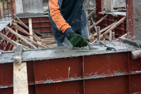 materiales de construccion: mano utilizando suavizar el solado de cemento con una llana
