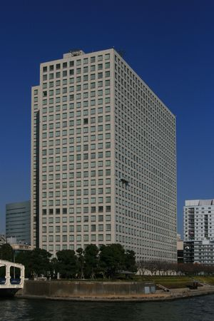 A skyscraper office building on the banks fo a river