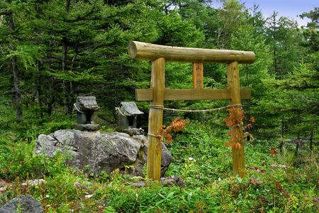 A Japanese shrine made of rock, located in a forest, with offerings still in place.