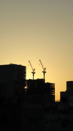 Two skyscrapper construction cranes in a siljouette against the yellow sky of a sun setting 写真素材
