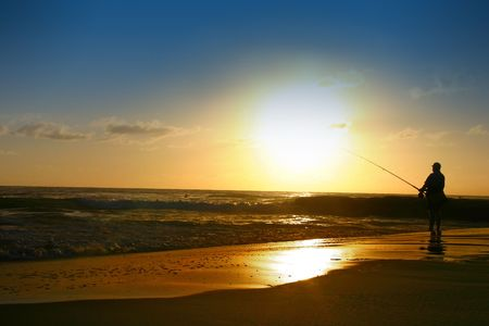 The sunrise over a beautiful Australian beach with silhouette of a man fishing
