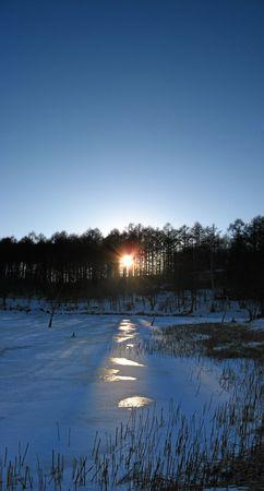 The sun shines through the tress to illumiate the frozen lake surface Stock Photo