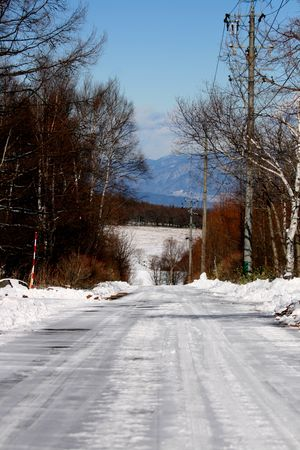 A snow covered road looking out to the vallery in winter
