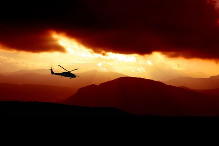 a rescue helicopter flys into a storm at sunset Stock Photo