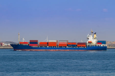 A cointaer vessel makes its way into port on a fine day. Stock Photo
