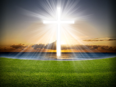background people: A cross in the sky with light rays at sunrise or sunset.