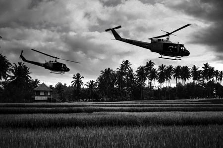 Vietnam War 'style' image circa 1970 two helicopters flying over South Vietnam looking for the North Vietnamese Army. (Artist's Impression) 版權商用圖片 - 67374606