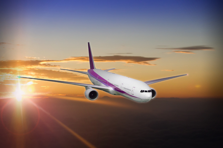 Modern commercial jet flying at sunset Stock Photo
