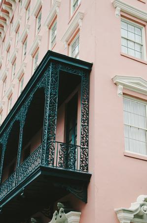 in charleston: Pink Charleston Building with Black Iron Balcony
