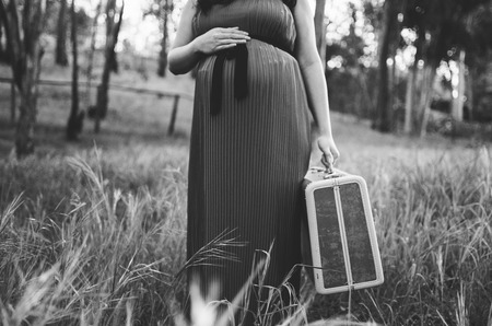 maxi dress: Pregnant Woman Holding Suitcase