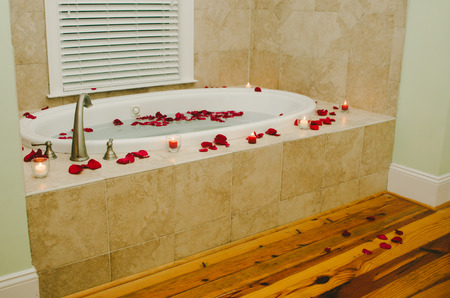 Romantic Bath Tub with Red Rose Petals Stock Photo