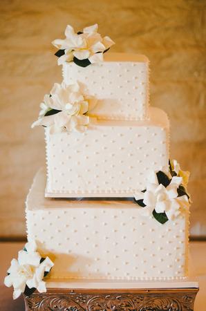 asymmetry: Ivory Square Layered Flower Wedding Cake Stock Photo