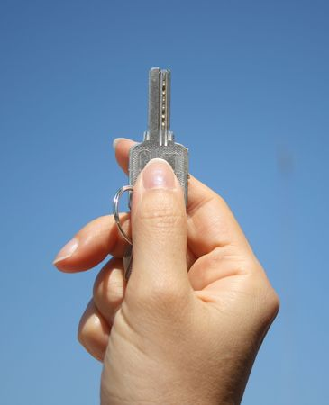 hand holds a key over blue background
