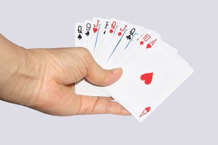 Hand and playing cards isolated on a gray background