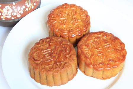 Moon cakes with Chinese teapot on white background. Consumed during Chinese mid-autumn festival  photo