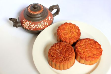 Moon cakes with Chinese teapot on white background. Consumed during Chinese mid-autumn festival  Stock Photo