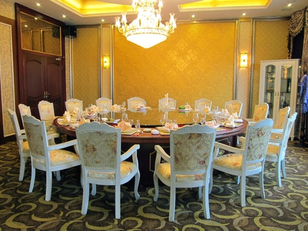 Restaurant dinning room with big table, closet and chandelier