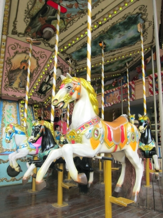 A view of some carousel horses in the amusement park
