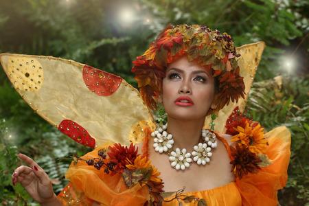 Asian model wearing an orange color fairy-tale costume having a fashion shoot Stock Photo