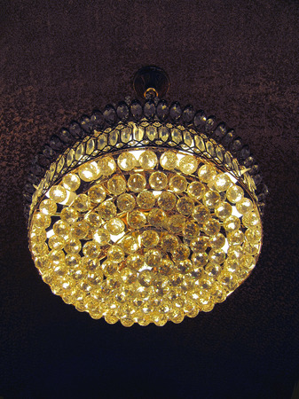 Chandelier hanging under a ceiling in a hotel lobby