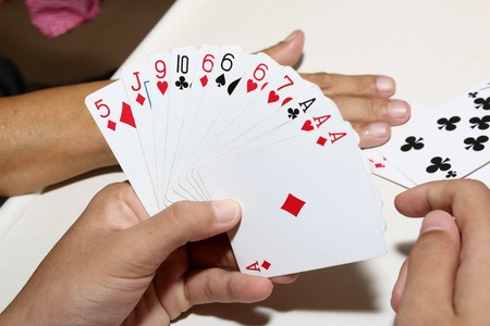 Playing cards in hand and on table