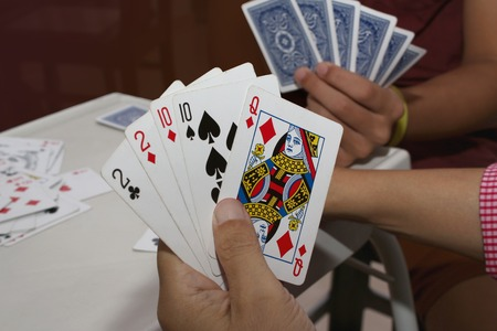 Playing cards in hand and on table during Chinese New Year